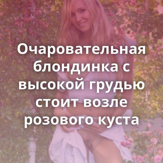 Очаровательная блондинка с высокой грудью стоит возле розового куста