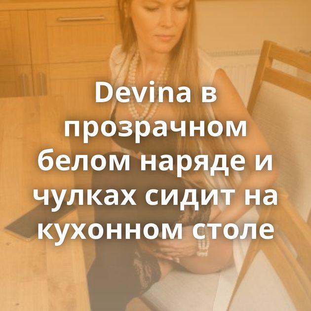 Devina в прозрачном белом наряде и чулках сидит на кухонном столе