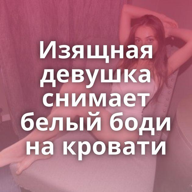 Изящная девушка снимает белый боди на кровати