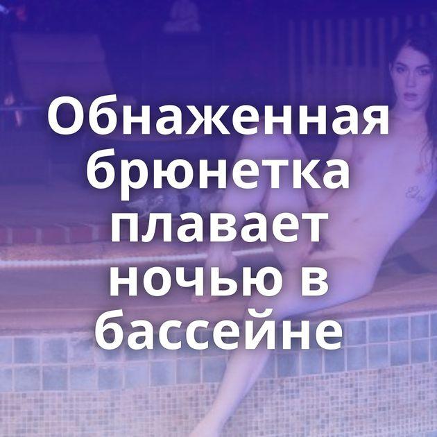 Обнаженная брюнетка плавает ночью в бассейне