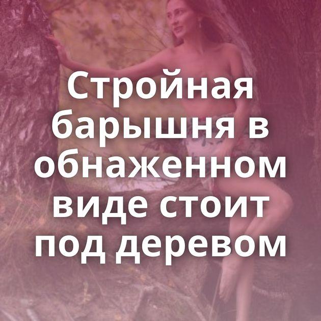 Стройная барышня в обнаженном виде стоит под деревом