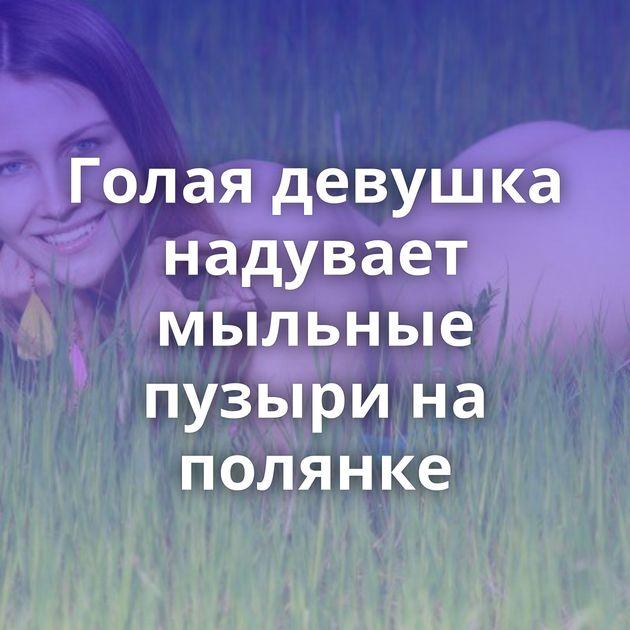 Голая девушка надувает мыльные пузыри на полянке