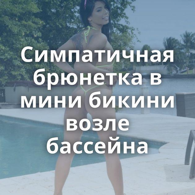 Симпатичная брюнетка в мини бикини возле бассейна