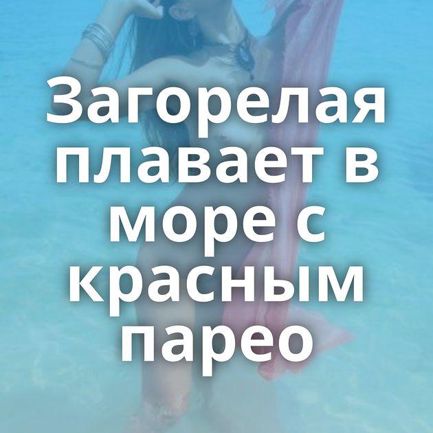 Загорелая плавает в море с красным парео