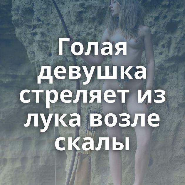 Голая девушка стреляет из лука возле скалы