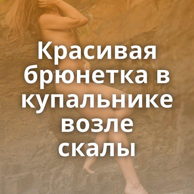 Красивая брюнетка в купальнике возле скалы