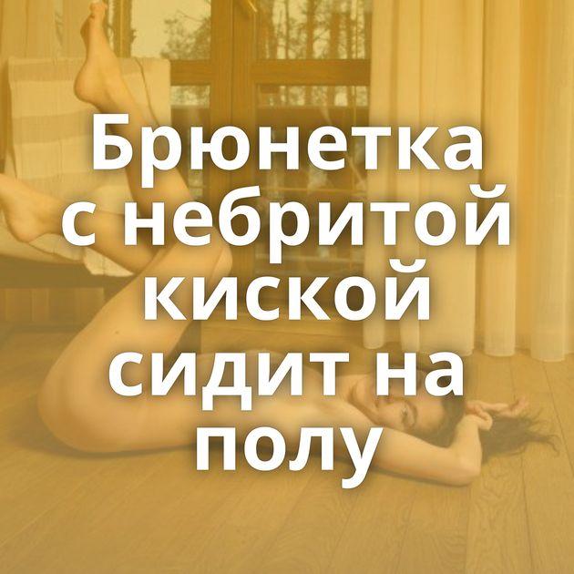 Брюнетка с небритой киской сидит на полу
