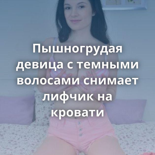 Пышногрудая девица с темными волосами снимает лифчик на кровати
