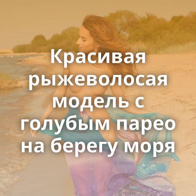 Красивая рыжеволосая модель с голубым парео на берегу моря