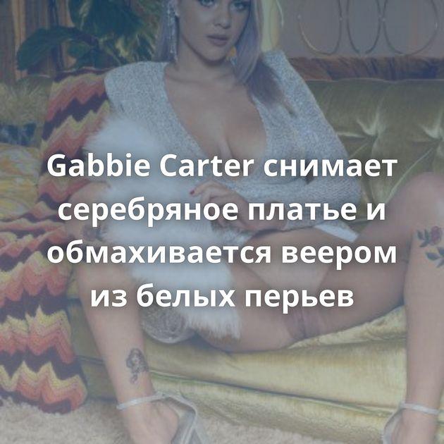 Gabbie Carter снимает серебряное платье и обмахивается веером из белых перьев