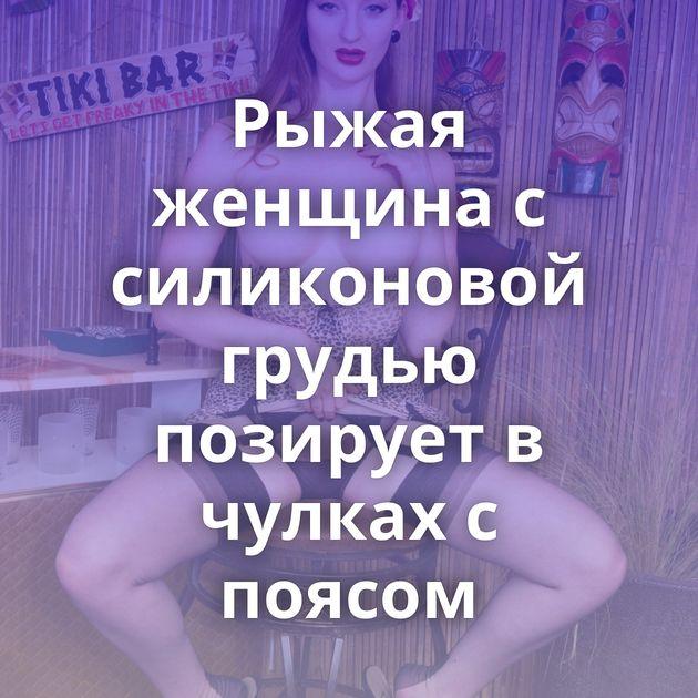 Рыжая женщина с силиконовой грудью позирует в чулках с поясом