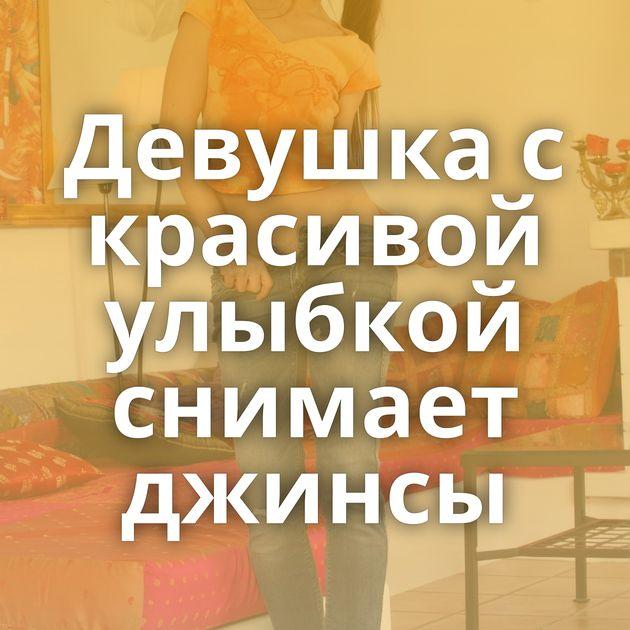 Девушка с красивой улыбкой снимает джинсы