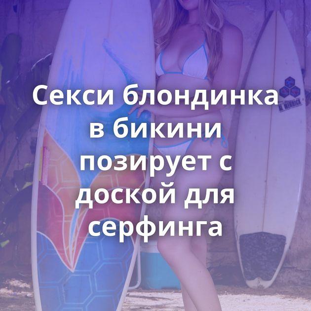 Секси блондинка в бикини позирует с доской для серфинга