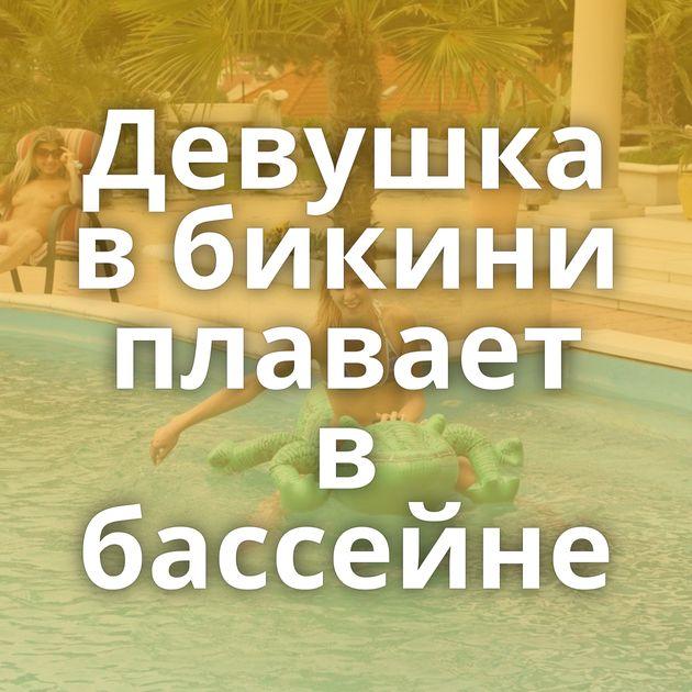 Девушка в бикини плавает в бассейне