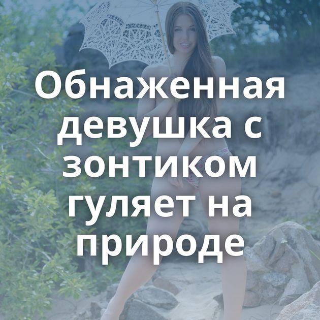 Обнаженная девушка с зонтиком гуляет на природе