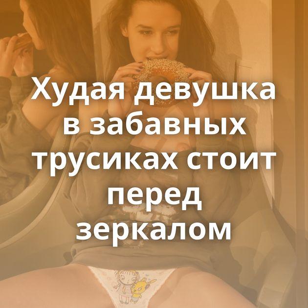 Худая девушка в забавных трусиках стоит перед зеркалом