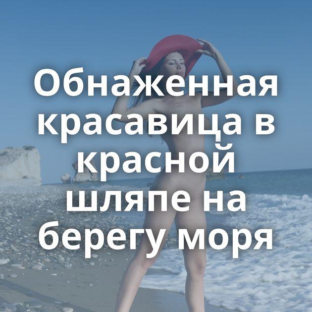 Обнаженная красавица в красной шляпе на берегу моря