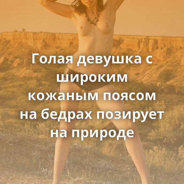 Голая девушка с широким кожаным поясом на бедрах позирует на природе