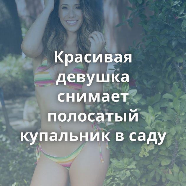 Красивая девушка снимает полосатый купальник в саду