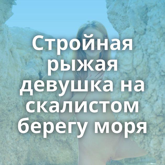 Стройная рыжая девушка на скалистом берегу моря