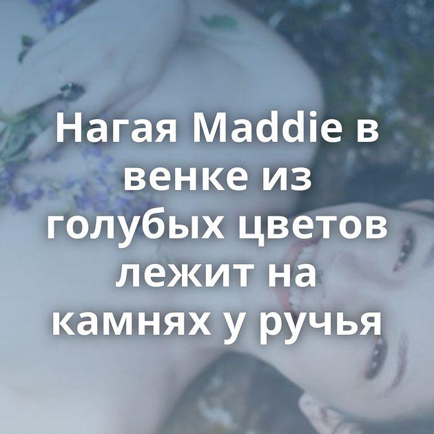 Нагая Maddie в венке из голубых цветов лежит на камнях у ручья