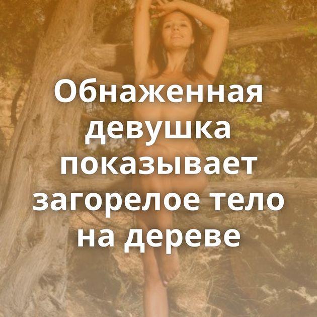 Обнаженная девушка показывает загорелое тело на дереве