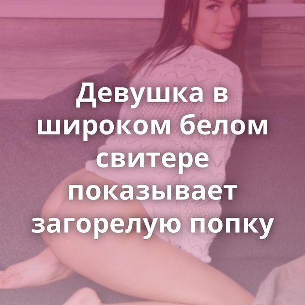 Девушка в широком белом свитере показывает загорелую попку