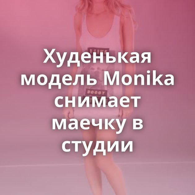 Худенькая модель Monika снимает маечку в студии