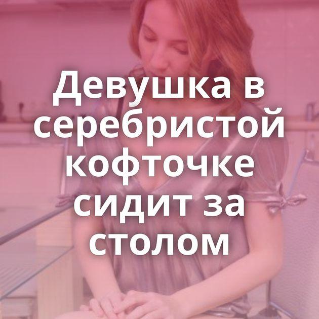 Девушка в серебристой кофточке сидит за столом