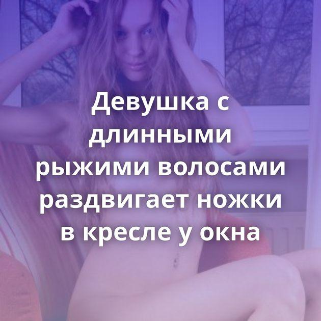 Девушка с длинными рыжими волосами раздвигает ножки в кресле у окна