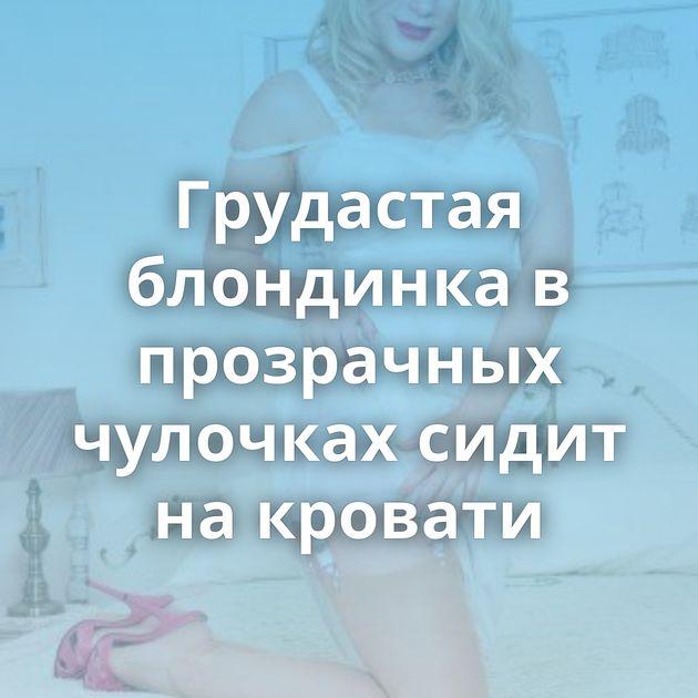 Грудастая блондинка в прозрачных чулочках сидит на кровати