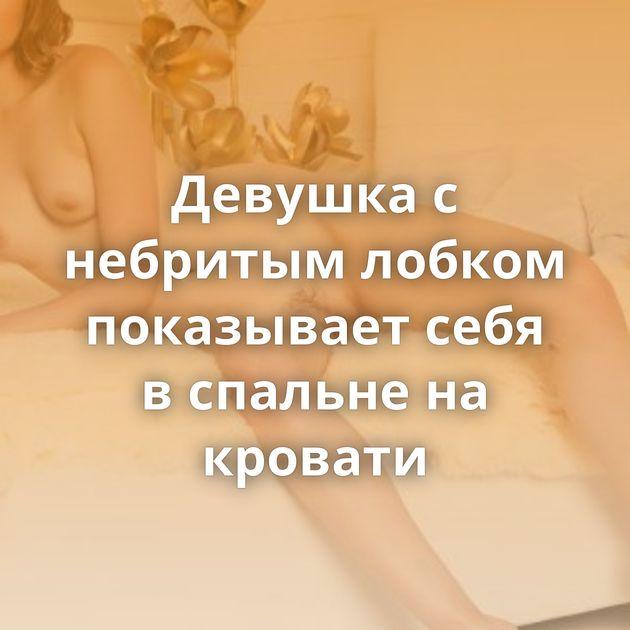 Девушка с небритым лобком показывает себя в спальне на кровати