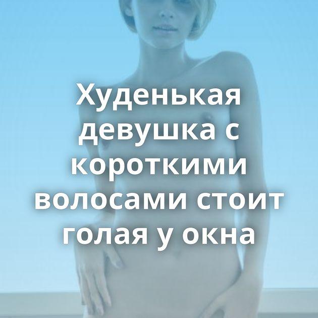 Худенькая девушка с короткими волосами стоит голая у окна