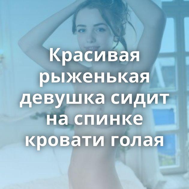 Красивая рыженькая девушка сидит на спинке кровати голая
