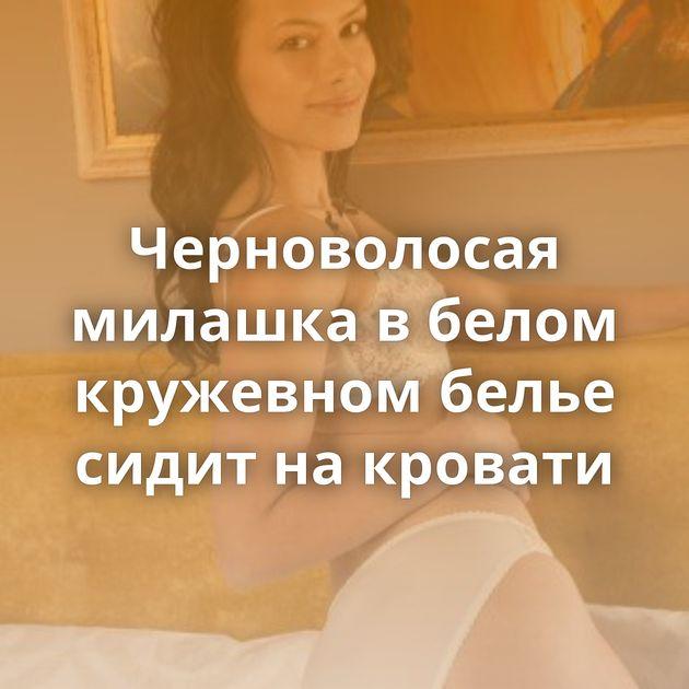 Черноволосая милашка в белом кружевном белье сидит на кровати