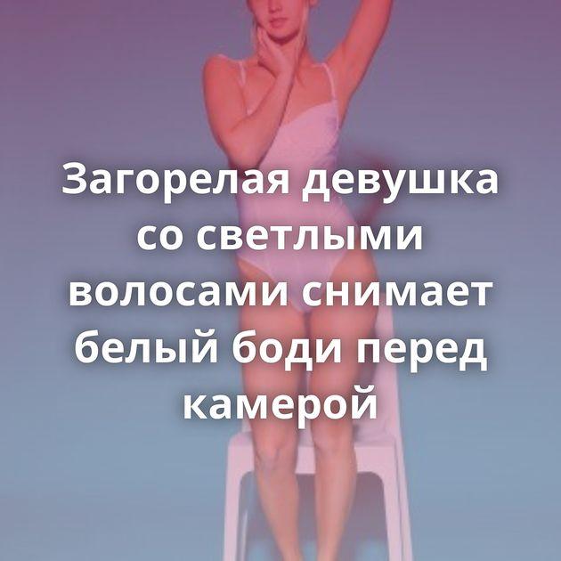 Загорелая девушка со светлыми волосами снимает белый боди перед камерой