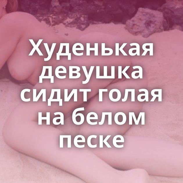 Худенькая девушка сидит голая на белом песке