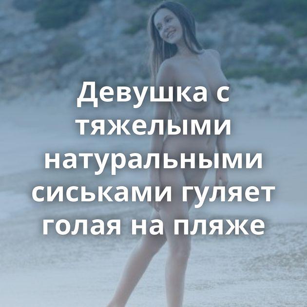 Девушка с тяжелыми натуральными сиськами гуляет голая на пляже