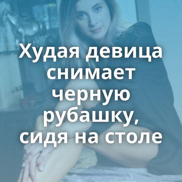 Худая девица снимает черную рубашку, сидя на столе
