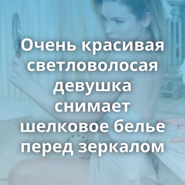 Очень красивая светловолосая девушка снимает шелковое белье перед зеркалом
