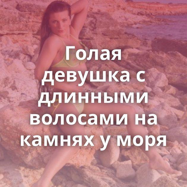 Голая девушка с длинными волосами на камнях у моря