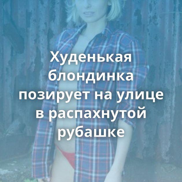 Худенькая блондинка позирует на улице в распахнутой рубашке