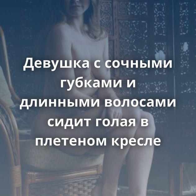 Девушка с сочными губками и длинными волосами сидит голая в плетеном кресле