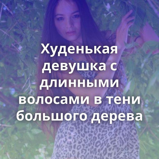 Худенькая девушка с длинными волосами в тени большого дерева