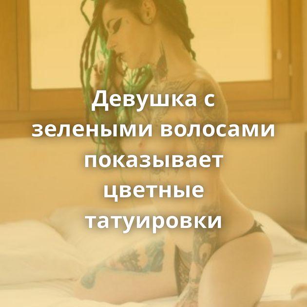 Девушка с зелеными волосами показывает цветные татуировки