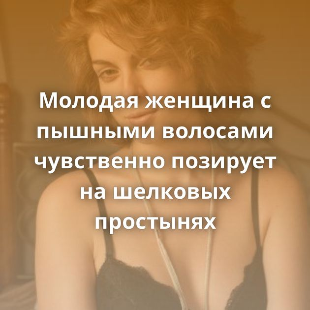 Молодая женщина с пышными волосами чувственно позирует на шелковых простынях