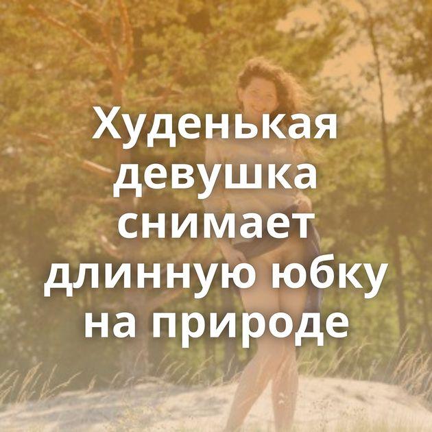 Худенькая девушка снимает длинную юбку на природе