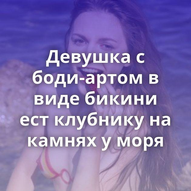 Девушка с боди-артом в виде бикини ест клубнику на камнях у моря