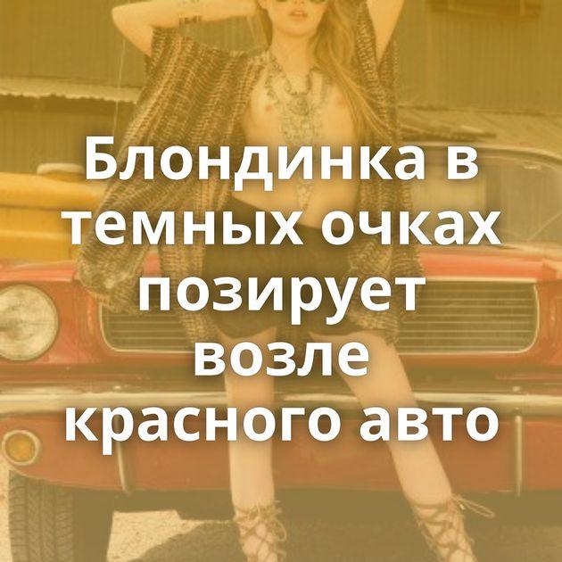 Блондинка в темных очках позирует возле красного авто