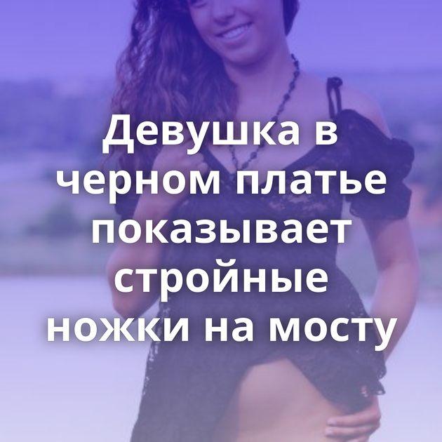 Девушка в черном платье показывает стройные ножки на мосту